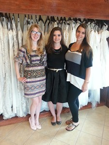 Students (left to right) Sydney, Renee, and Maria standing in front of the customizable dresses at Splendid Bridal